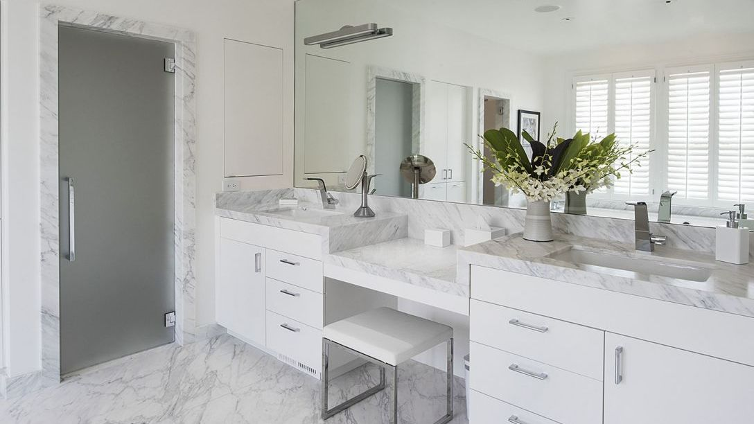 Master bathroom of Pacific Heights remodel with twin sinks, white marble floors and countertops, and white cabinets.