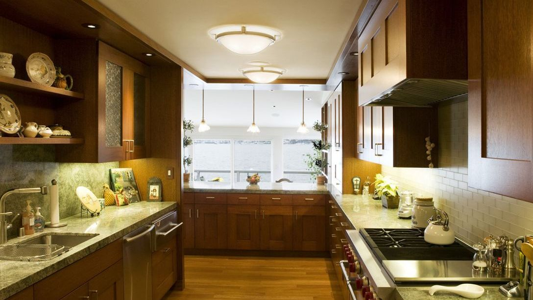 Water Front remodel kitchen with wooden floors and cabinets, gas stove, and green countertop.