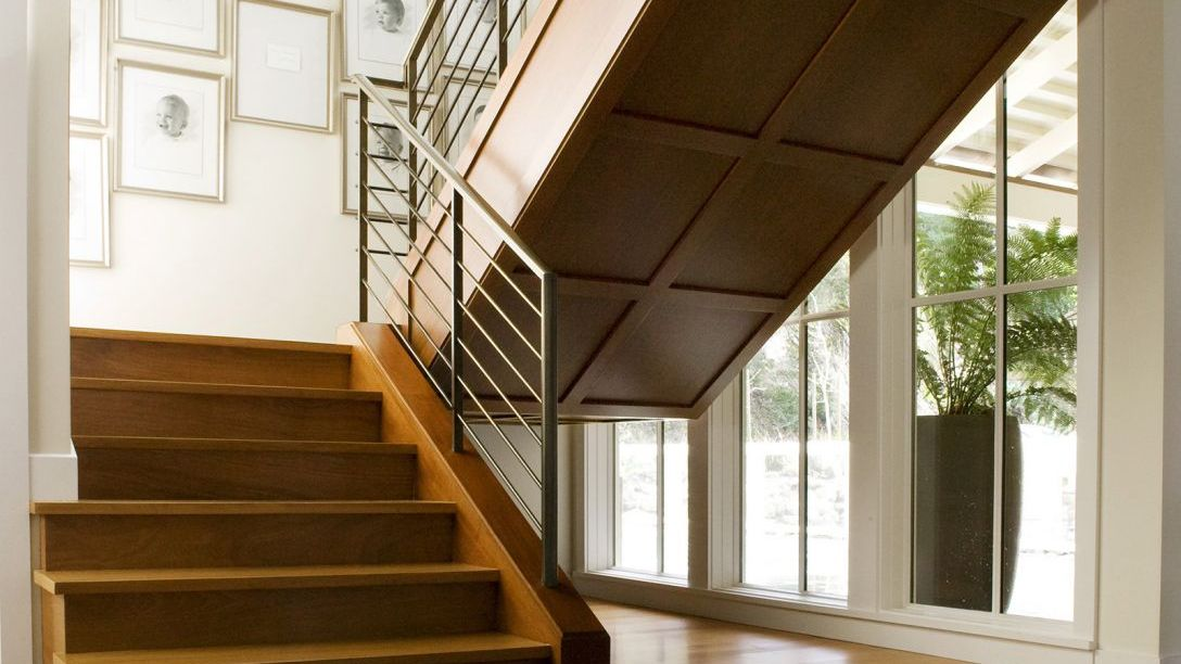 Bottom of wooden staircase with metal railing in Water Front remodel.