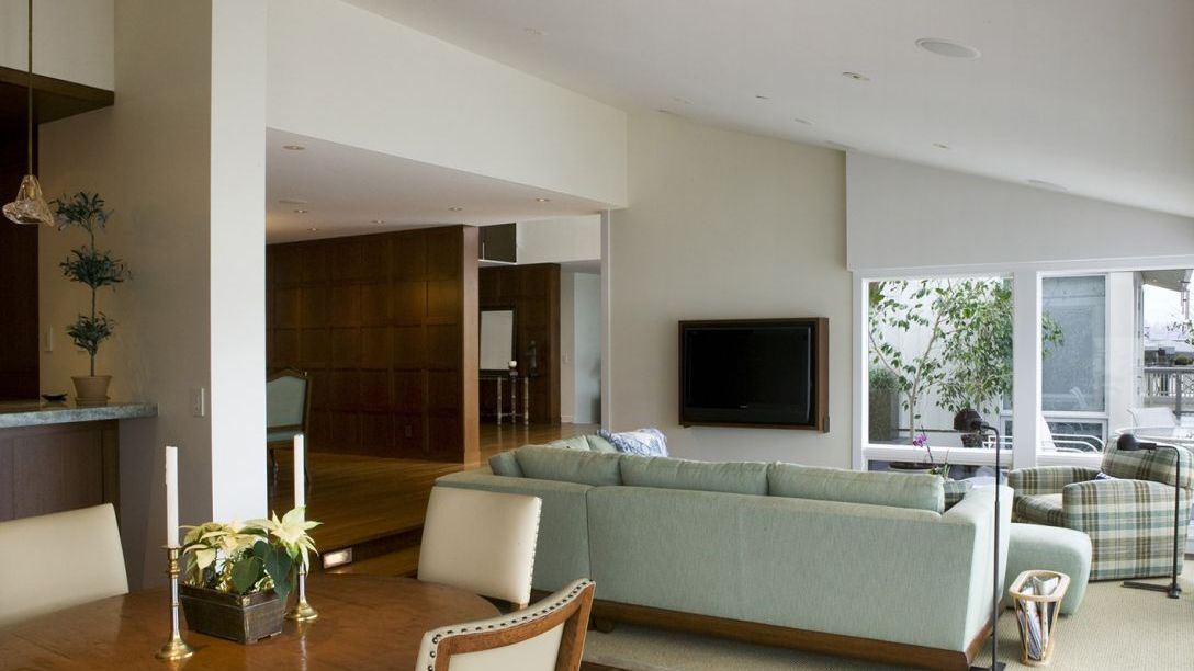 Family room of Water Front remodel with tv mounted on the wall and seafoam green couch.